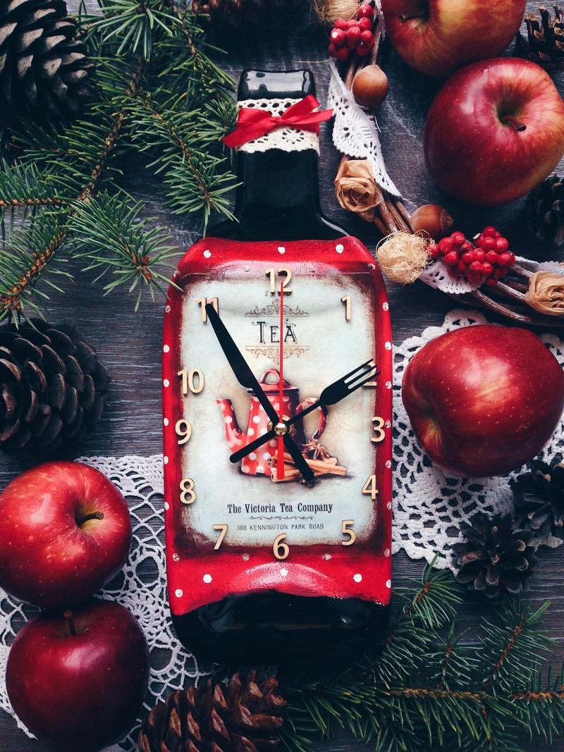 Настенные часы из стеклянной бутылки, в них установлены бесшумные часовые механизмы. В оформлении используется две техники: декупаж (50%) и ручная роспись акрилом (50%). Часы покрыты лаком. Изображение на часах можно сделать на заказ, например с тематикой города и его названием (если это курорт) или можно сделать партию одинаковых изображений с логотипом фирмы (на корпоративный подарок).